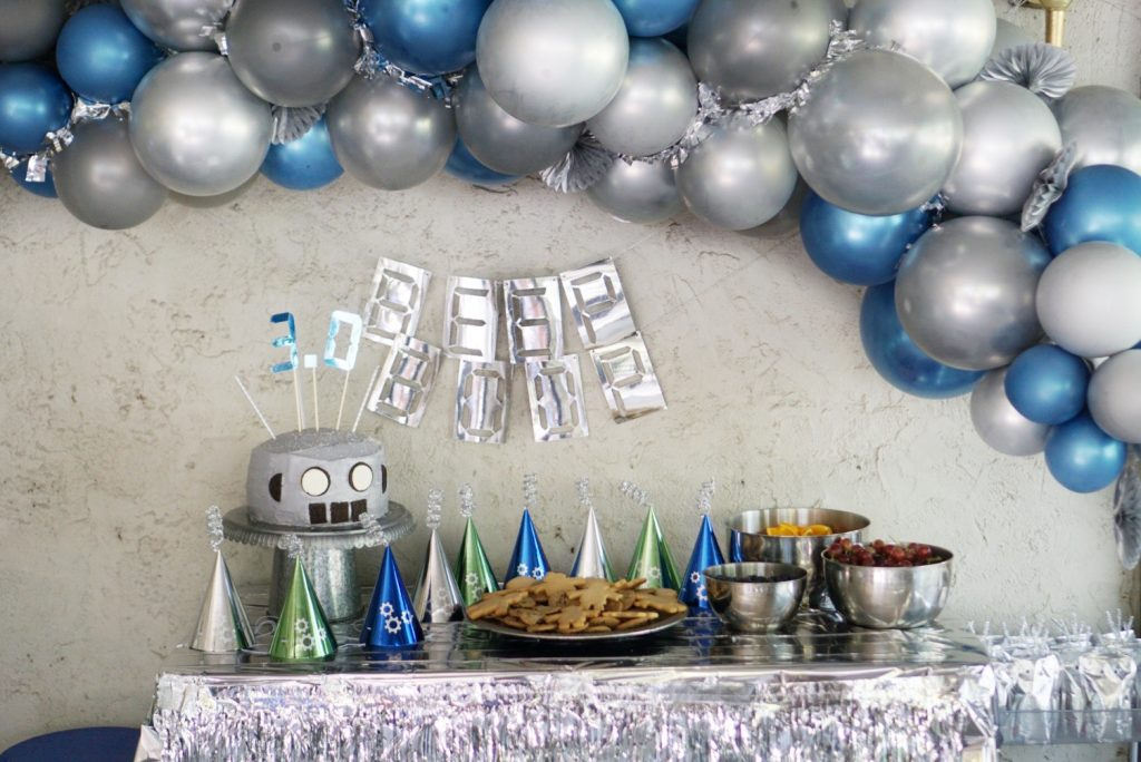 DIY Balloon Arches & Swags - Robot themed birthday party features a metallic silver and blue balloon arch with tinsel and gear embellishments.  #partyballoons #DIYBalloons #DIYBalloonArch #DIYBalloonSwag #BalloonArch #BalloonSwag #RobotParty #RobotBirthdayParty #Partyideas